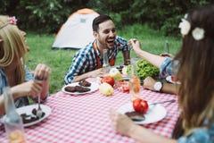 Amis gais s'asseyant à la table et ayant le repas Photo stock