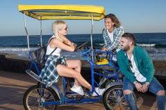 Amis gais s'asseyant ensemble sur le chariot Photos stock