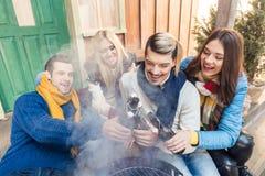 Amis gais s'asseyant sur le porche avec de la bière sur le barbecue Photos libres de droits