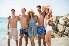 Amis gais se tenant à la plage pendant le jour ensoleillé Photographie stock