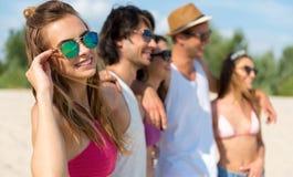 Amis gais se tenant sur la plage Image stock