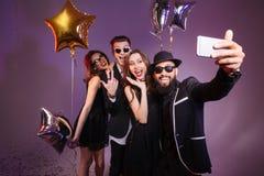 Amis gais souriant et faisant le selfie ensemble Photographie stock
