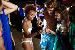 Amis gais souriant, se réjouissant, se reposant à la partie près de la piscine Photo stock