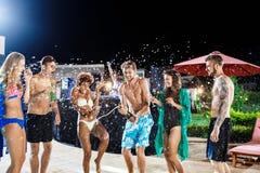 Amis gais souriant, se réjouissant, se reposant à la partie près de la piscine Photographie stock libre de droits