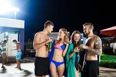 Amis gais souriant, se réjouissant, se reposant à la partie près de la piscine Image libre de droits