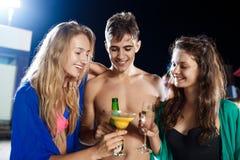 Amis gais souriant, se réjouissant, se reposant à la partie près de la piscine Photos libres de droits