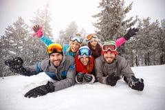 Amis gais sur le ski s'étendant ensemble sur la neige Images stock