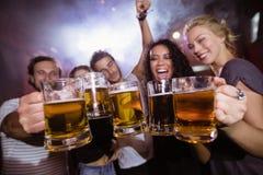 Amis gais tenant des tasses de bière ensemble Photos libres de droits