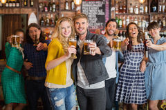 Amis gais tenant des verres de bière dans le bar Images libres de droits