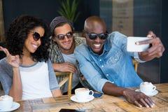 Amis gais utilisant des lunettes de soleil tout en prenant le selfie dans le café Image libre de droits