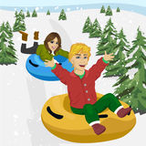 Amis glissant vers le bas sur des tubes de neige Photographie stock
