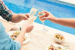 Amis grillant à la partie par la piscine Photos libres de droits