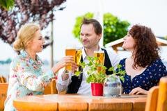 Amis grillant avec de la bière dans le restaurant Images libres de droits
