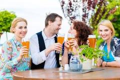 Amis grillant avec de la bière dans le restaurant Photographie stock