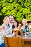 Amis grillant avec de la bière dans le restaurant Image stock