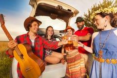 Amis grillant avec de la bière se reposant dans une botte de voiture Images libres de droits