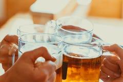 Amis grillant avec des verres de bière blonde au bar Image stock
