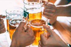 Amis grillant avec des verres de bière blonde au bar Images stock
