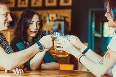 Amis grillant avec des verres de bière blonde au bar Photos libres de droits