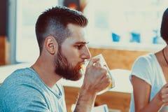 Amis grillant avec des verres de bière blonde au bar Photo libre de droits