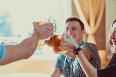 Amis grillant avec des verres de bière blonde au bar Photographie stock libre de droits