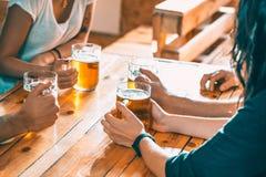 Amis grillant avec des verres de bière blonde au bar Photo stock