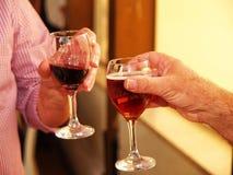 Amis grillant avec deux verres de vin rouge Photo stock