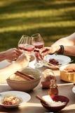 Amis grillant avec du vin au-dessus d'un repas de spaghetti Photographie stock