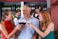 Amis grillant avec un verre de vin rouge dans une barre Photo libre de droits