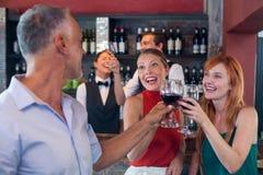 Amis grillant avec un verre de vin rouge dans une barre Photo stock