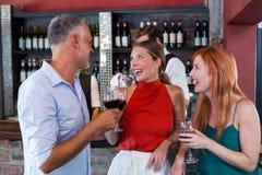Amis grillant avec un verre de vin rouge dans une barre Image stock