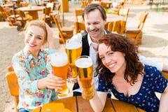Amis grillant dans le restaurant de jardin Images libres de droits