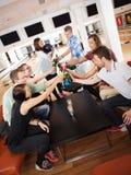 Amis grillant des boissons dans le club de bowling Images libres de droits