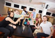 Amis grillant des boissons dans le club de bowling Image libre de droits