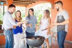 Amis grillant des hamburgers et profiter d'un agréable moment Image stock
