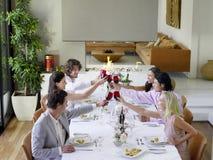 Amis grillant des verres à vin à travers le Tableau de dîner Photo stock