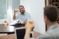 Amis grillant des verres de bière Image libre de droits