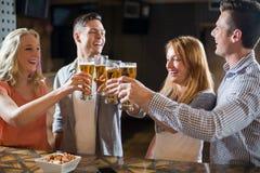 Amis grillant des verres de bière au compteur de barre Photo stock