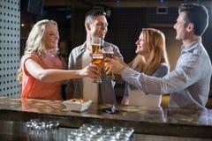 Amis grillant des verres de bière au compteur de barre Image libre de droits