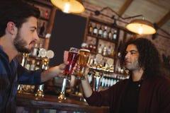 Amis grillant des verres de bière au compteur de barre Images stock