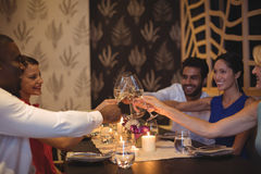 Amis grillant des verres de champagne dans le restaurant Image libre de droits