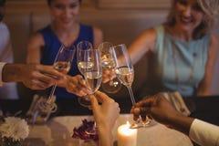 Amis grillant des verres de champagne dans le restaurant Photographie stock libre de droits