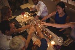 Amis grillant des verres de champagne dans le restaurant Photo libre de droits