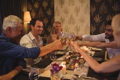 Amis grillant des verres de champagne dans le restaurant Image stock