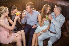 Amis grillant des verres de cocktail dans la barre Photographie stock libre de droits