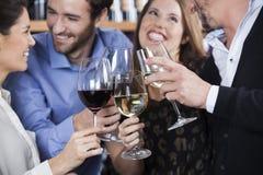 Amis grillant des verres de vin à la boutique Photographie stock