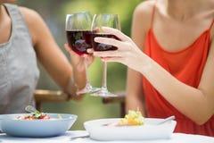 Amis grillant des verres de vin dans le restaurant Photo stock