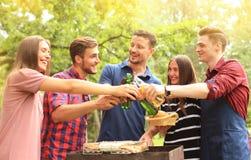 Amis grillant la bière au barbecue en nature Photographie stock