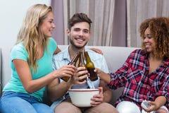 Amis grillant la bière tout en regardant le match de football Image libre de droits