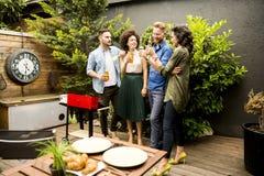 Amis grillant la nourriture et appréciant la partie de barbecue Photo libre de droits